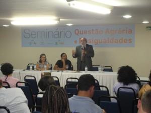 O ministro Gilberto Carvalho, falando ao microfone. À esquerda, sentado, com a mão no rosto, Pedro Stédile líder do MST