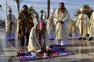 Dom Cristian Contreras, bispo de Melipilla (Chile), ajoelhado diante do altar pagão. Observa-o Dom Moisés Atisha, novo bispo de Arica, que também faria o mesmo