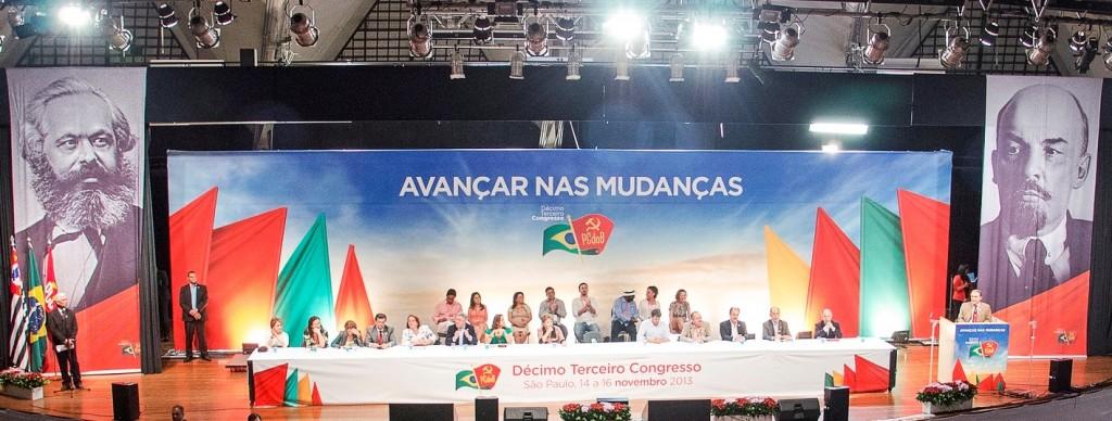 No centro da mesa, a Presidente Dilma Rousseff no 13º Congresso do Partido Comunista do Brasil. A bandeira da foice e martelo escondendo a bandeira do Brasil. Nas extremidades quadros de Marx e Lenin...