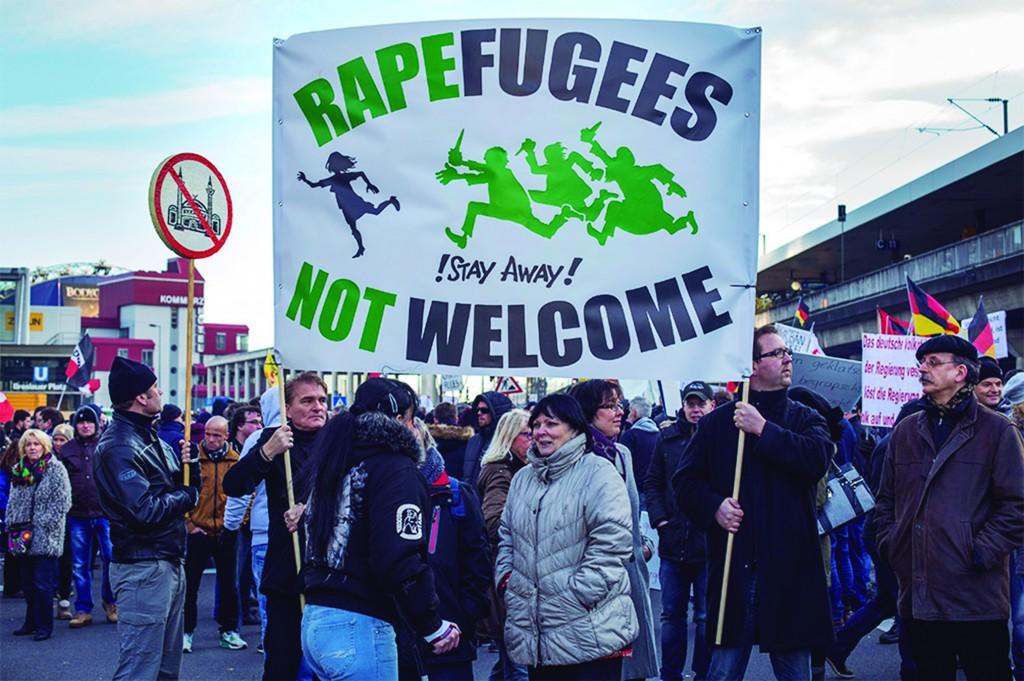 """Tradução do cartaz principal: """"Refugiados violadores! Fiquem longe! Não são bem-vindos"""""""