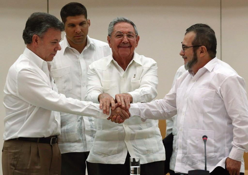 """O ditador Raúl Castro junta as mãos do presidente da Colômbia Juan Manuel Santos (esq.) e do chefe guerrilheiro """"Timochenko"""" (dir.) em Havana"""