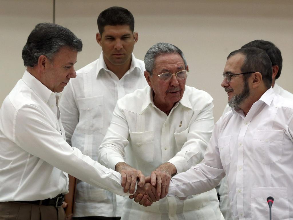 """À esq., Santos, o presidente colombiano, aperta a mão do líder terrorista das FARC, Rodrigo Londono, no anunciado """"acordo de paz"""" selado pelo ditador cubano Castro (no centro)"""