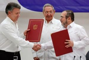 O presidente Santos cumprimenta o guerrilheiro Timochenko sob o olhar satisfeito de Raul Castro, no fim das conversações em Havana