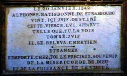 """A lápide registra a milagrosa conversão:  """"20 de janeiro de 1842, Alphonse Ratisbonne de Strasbourg veio aqui judeu obstinado. Esta Virgem lhe apareceu tal qual Você a vê (quadro acima). Tendo caído judeu, levantou-se cristão. — Estrangeiro, leve consigo a preciosa recordação da misericórdia de Deus e do poder de Nossa Senhora""""."""