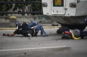 Carros de combate da Guarda Nacional Bolivariana passa por cima de manifestantes na  capital venezuelana