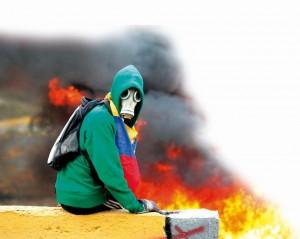 Jovem com máscara para se proteger das bombas de gás lacrimogêneo lançadas contra a população