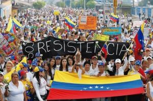 Opositores carregam uma imagem de Nossa Senhora do Carmo durante manifestação de protesto contra Maduro e sua repressão ditatorial. À esquerda, jovem com máscara contra bombas de gás lacrimogêneo.