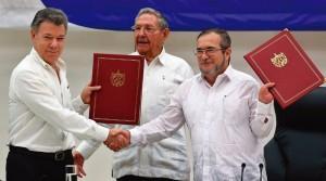 """O presidente colombiano, Santos, com Raul Castro e o líder guerrilheiro das FARC, """"Timochenko"""" com o texto do """"Acordo de Paz"""" em mãos."""