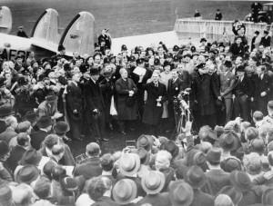 Neville Chamberlain, em sua chegada ao aeroporto de Heston (Londres), em 30 de Setembro de 1938, após seu encontro com Hitler em Munique. Em sua mão ele tem o acordo de paz feito entre Reino Unido e Alemanha.