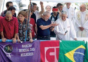 Curiosamente, as batinas que não vimos na foto acima, aqui elas aparecem... Se não usam mais batinas nos ambiente religiosos, por que usá-las numa manifestação comunista?