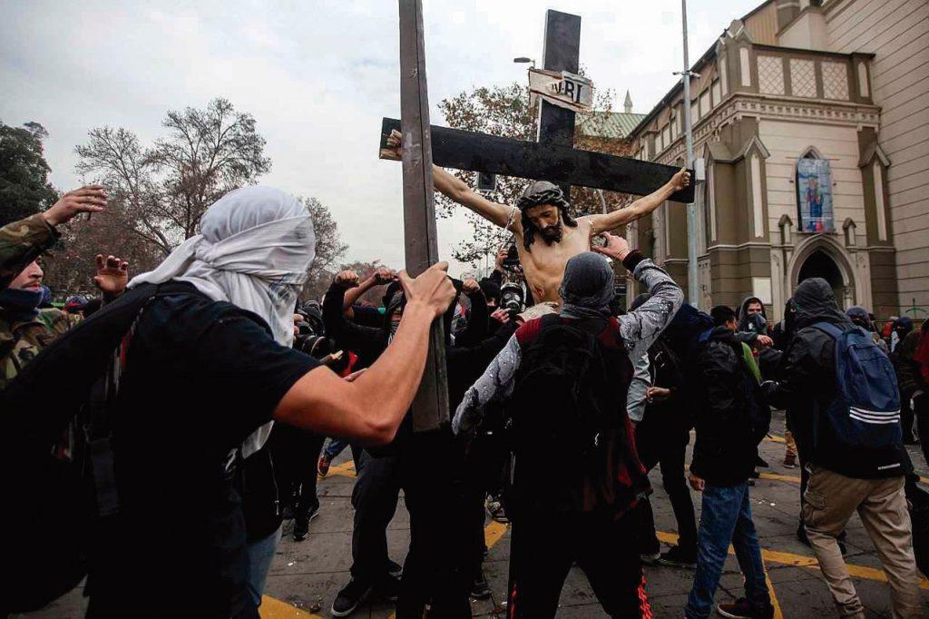 Violenta manifestação esquerdista profana igreja no centro de Santiago do Chile e retira de seu interior, sem nenhuma reação dos presentes, um antigo Crucifixo, que é brutal e sacrilegamente golpeado, atirado ao chão e quebrado.
