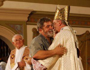 Lula sendo abraçado pelo Cardeal Dom Cláudio Hummes, observado pelo Bispo Dom Sandalo Bernardino