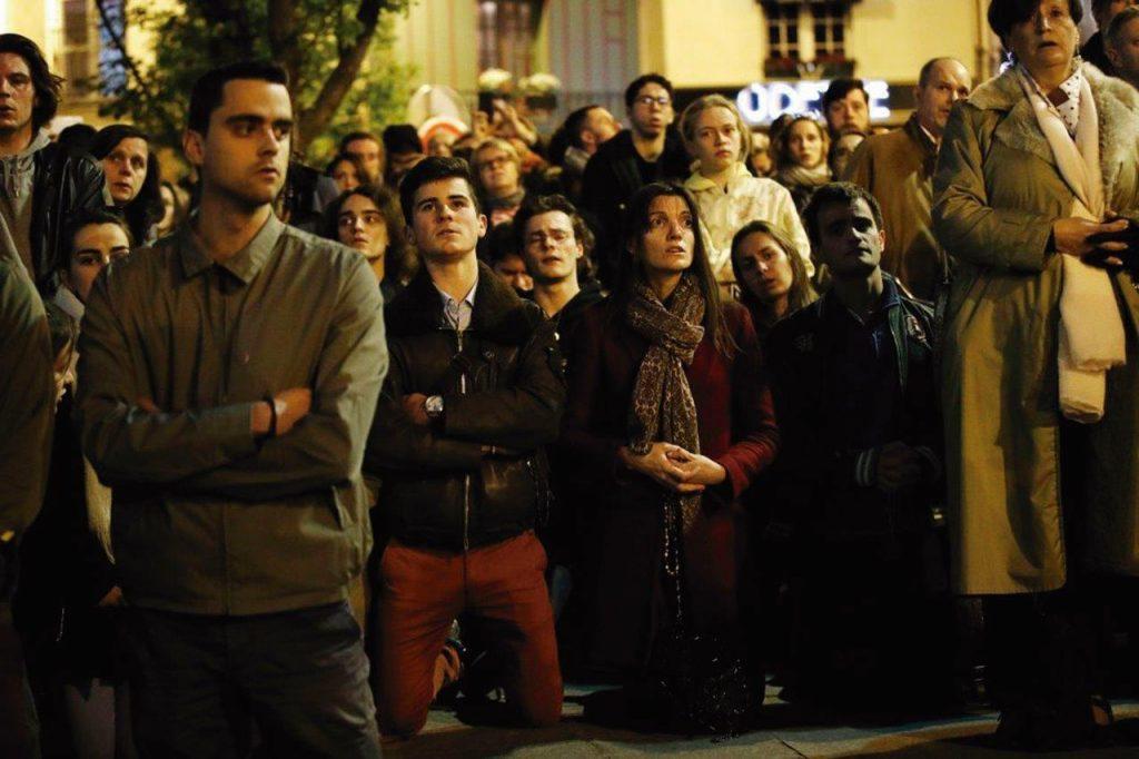 Jovens rezam diante de Notre-Dame em chamas